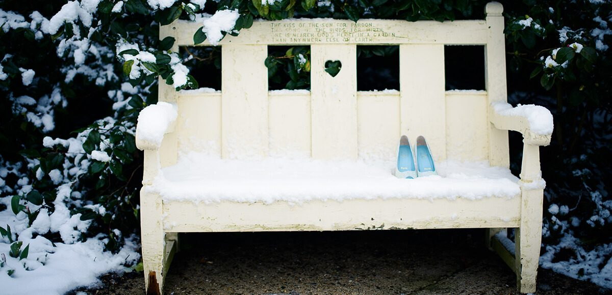 The bride's wedding shoes sit on a white bench surrounded by snow covered trees