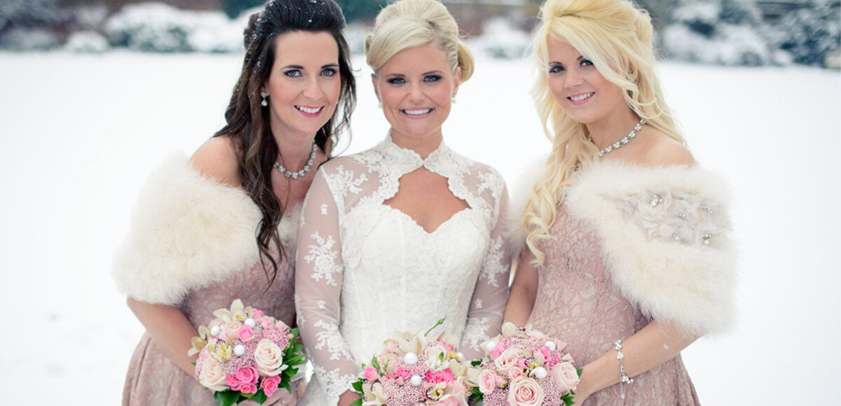 The bride and her two bridesmaids are dressed beautifully for a winter wedding wearing white boleros
