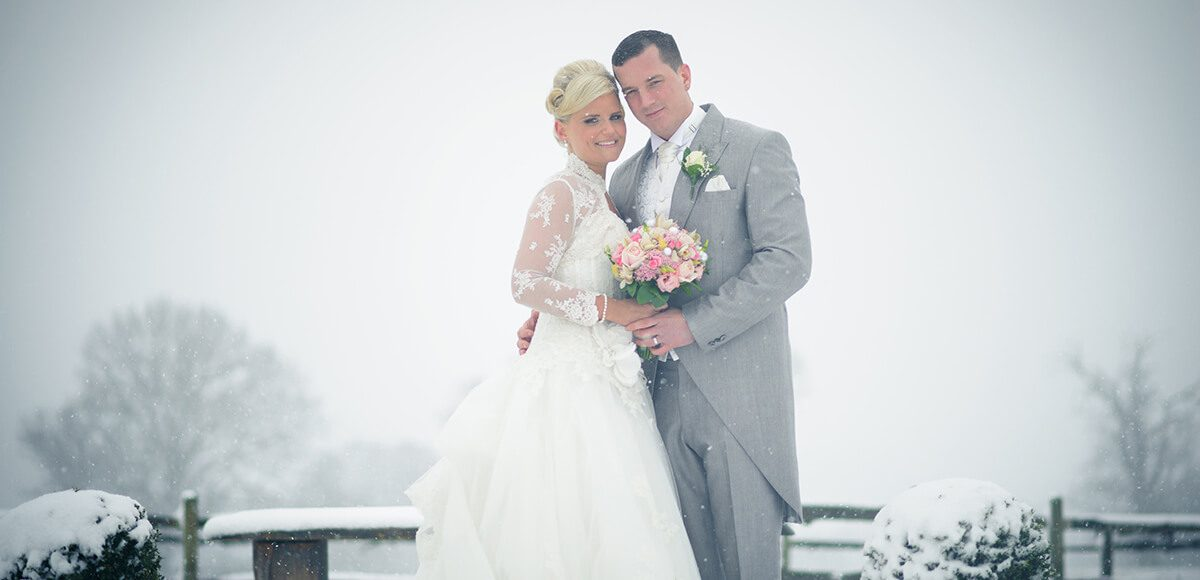 The happy couple steal a moment in the snow covered Walled Garden at Gaynes Park