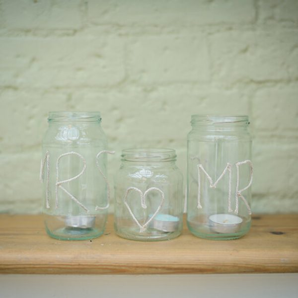 Three glass jars each containing a tea light are decorated with the words Mr and Mrs – wedding ideas