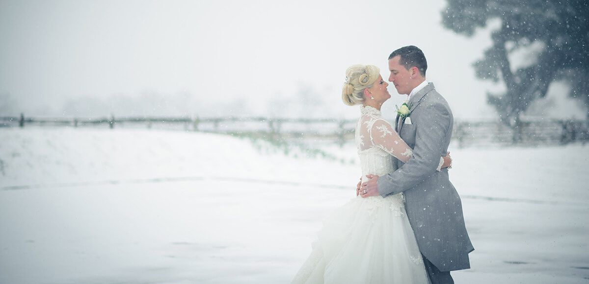 The bride and groom share an embrace in the stunning Walled Garden covered with a blanket of snow