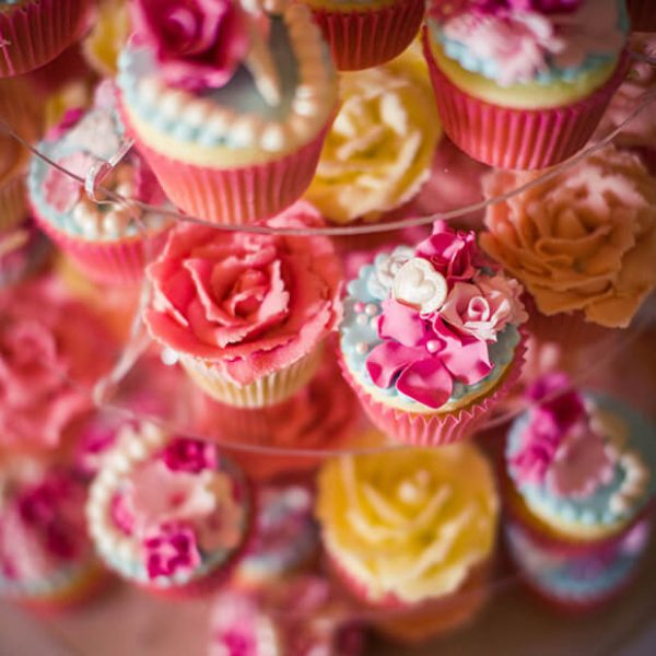 A close up of the couple's wedding cake which was a tower of pink and yellow cupcakes – wedding ideas