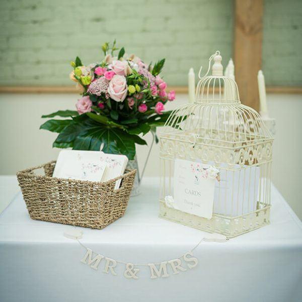 A wicker basket and whit birdcage for wedding cards beautifully reflects the couple's vintage wedding theme