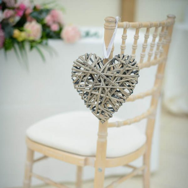 A wicker heart hangs from a white wooden chair in the wedding ceremony room – wedding decoration ideas