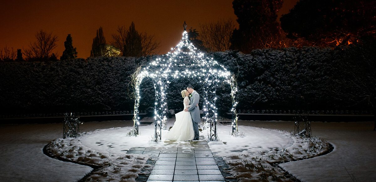 The happy newlyweds steal a kiss under the romantically lit iron Pavilion in the Walled Garden