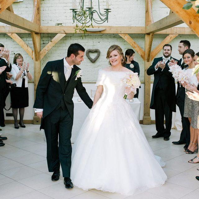Bride and groom walking down the aisle in the Orangery at Gaynes Park – wedding venues in Essex