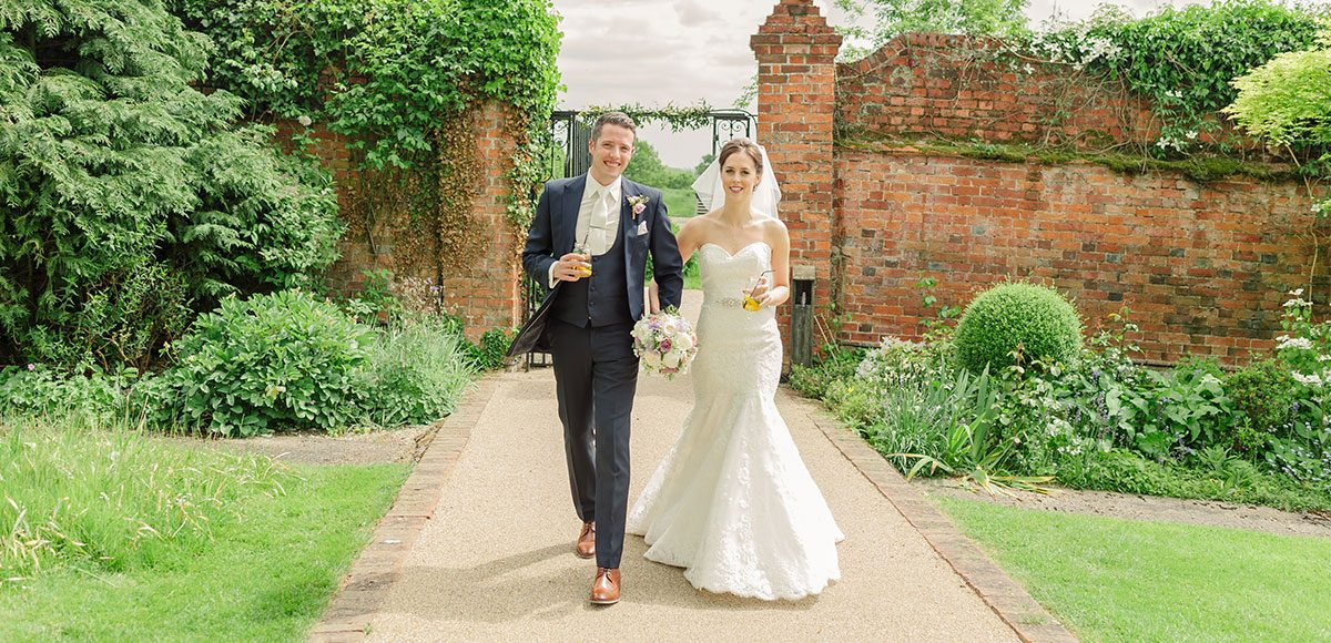 Bride and groom in the gardens of Gaynes Park wedding venue in Essex