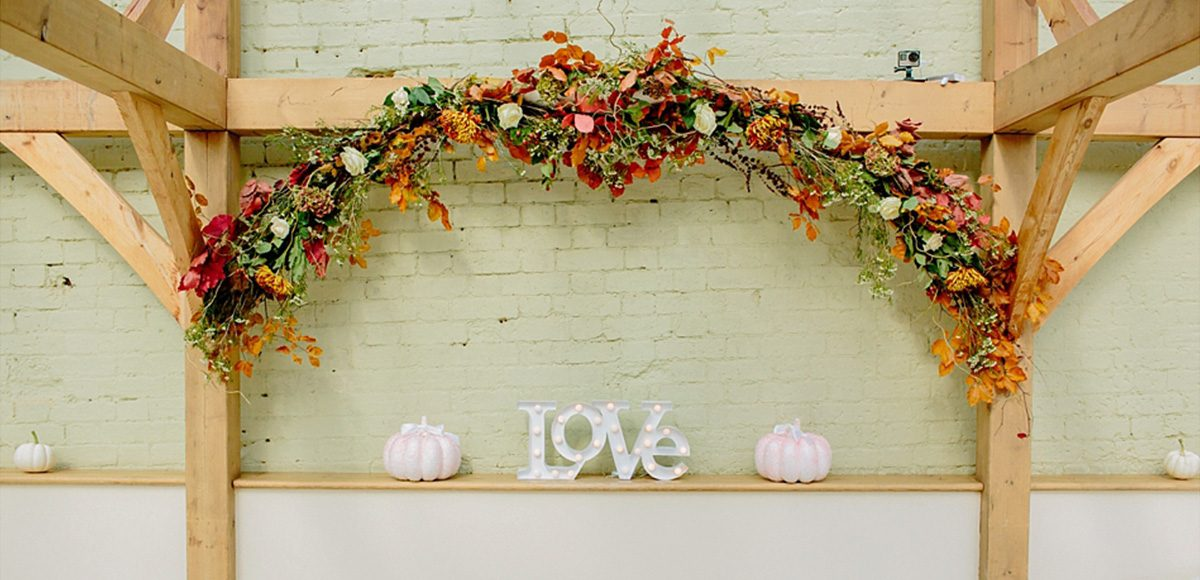 An autumnal arch of orange and red flowers and leaves decorating the Orangery at Gaynes Park