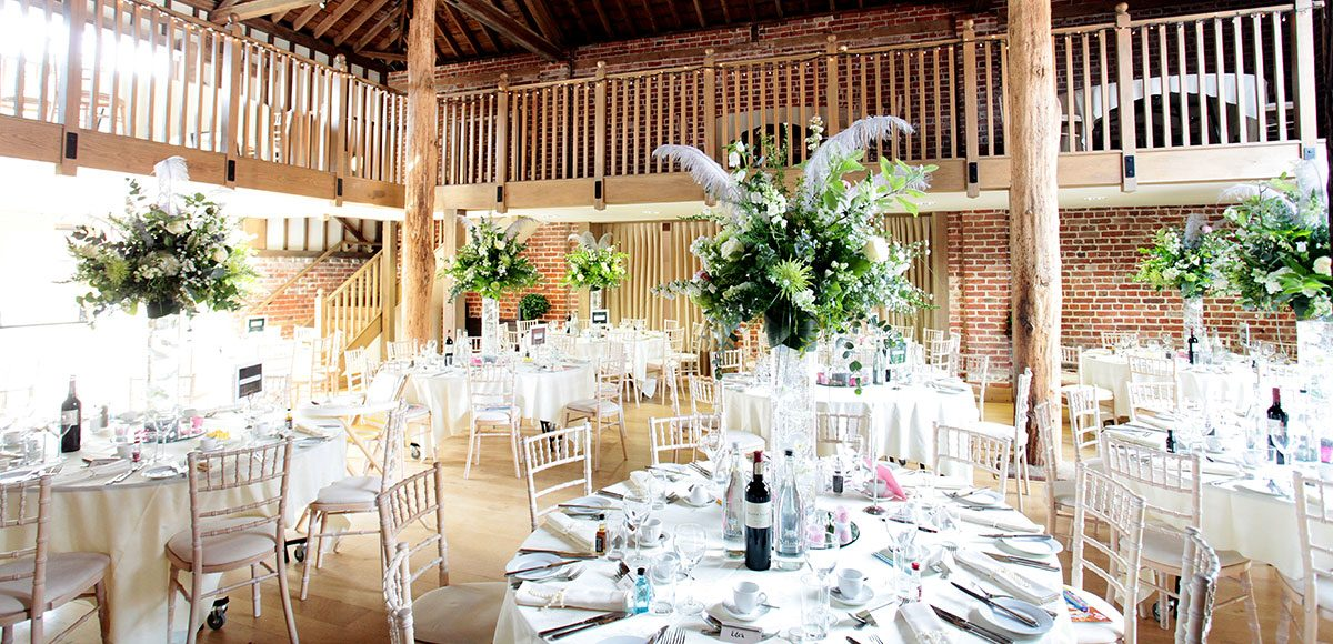 Tall flower vases as wedding centrepieces for an Essex barn wedding