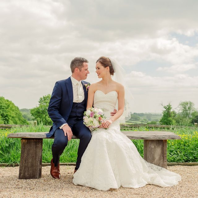 Bride and groom relaxing on a bench outside of their wedding venue