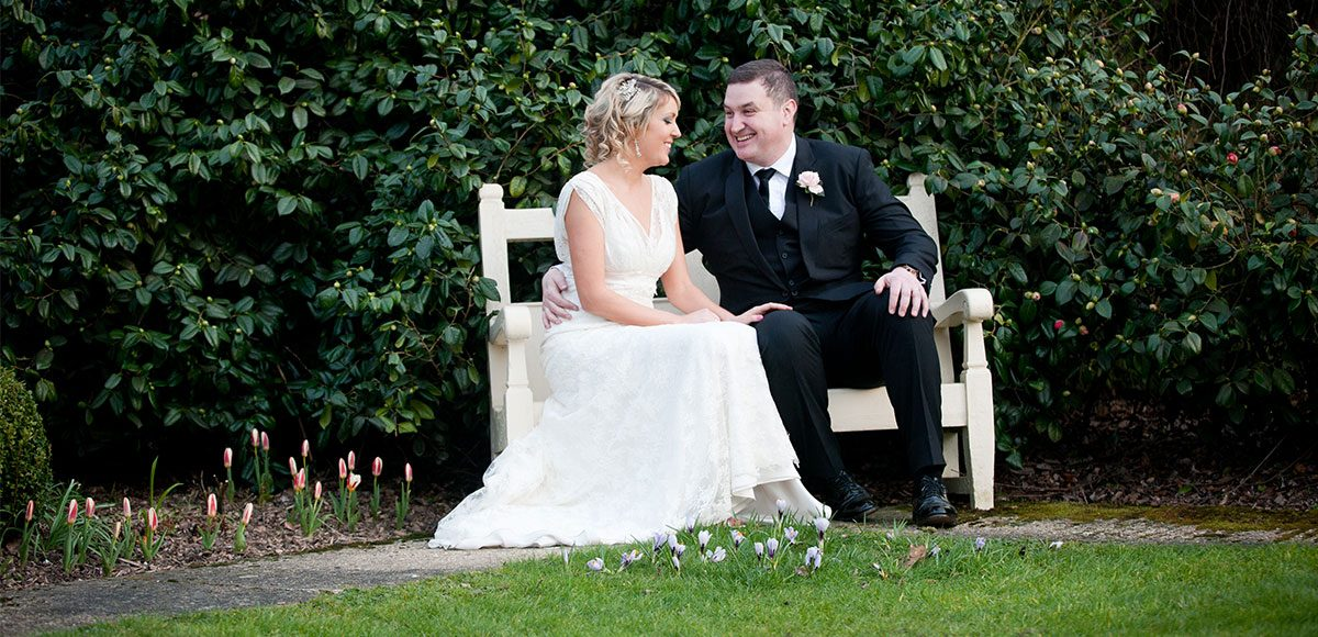 Bride and groom relaxing outside on a bench – barn wedding venues