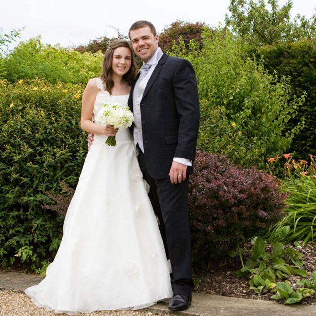 Bride and groom in the gardens of Gaynes Park wedding venue in Essex