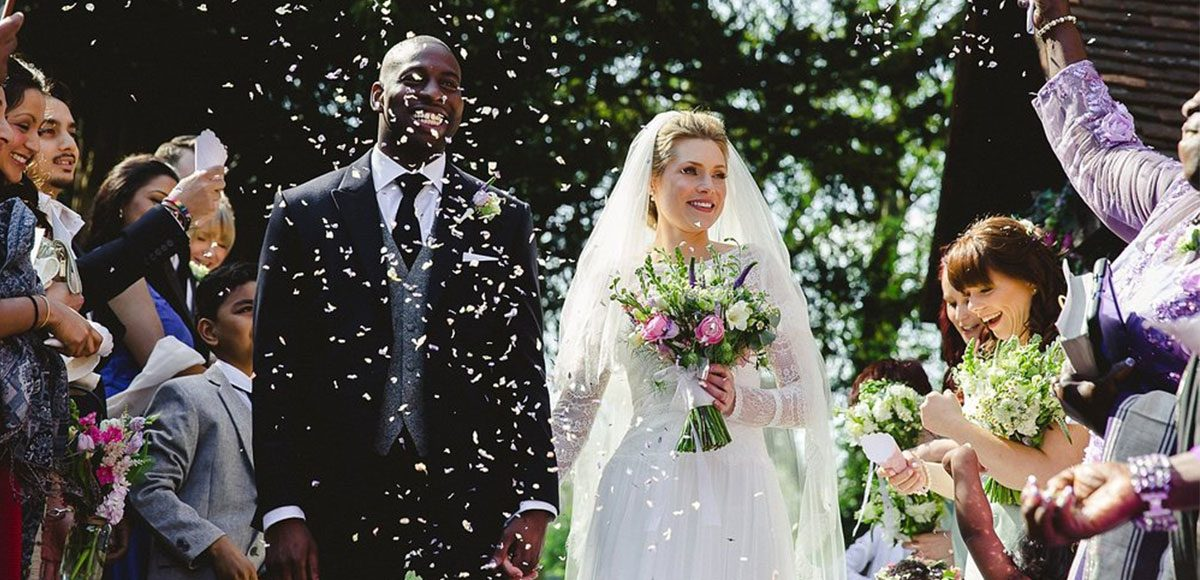 Wedding guests throw confetti over bride and groom
