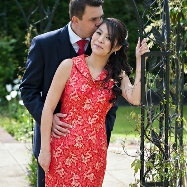 Bride wearing red wedding dress posing in the gardens of Gaynes Park with groom