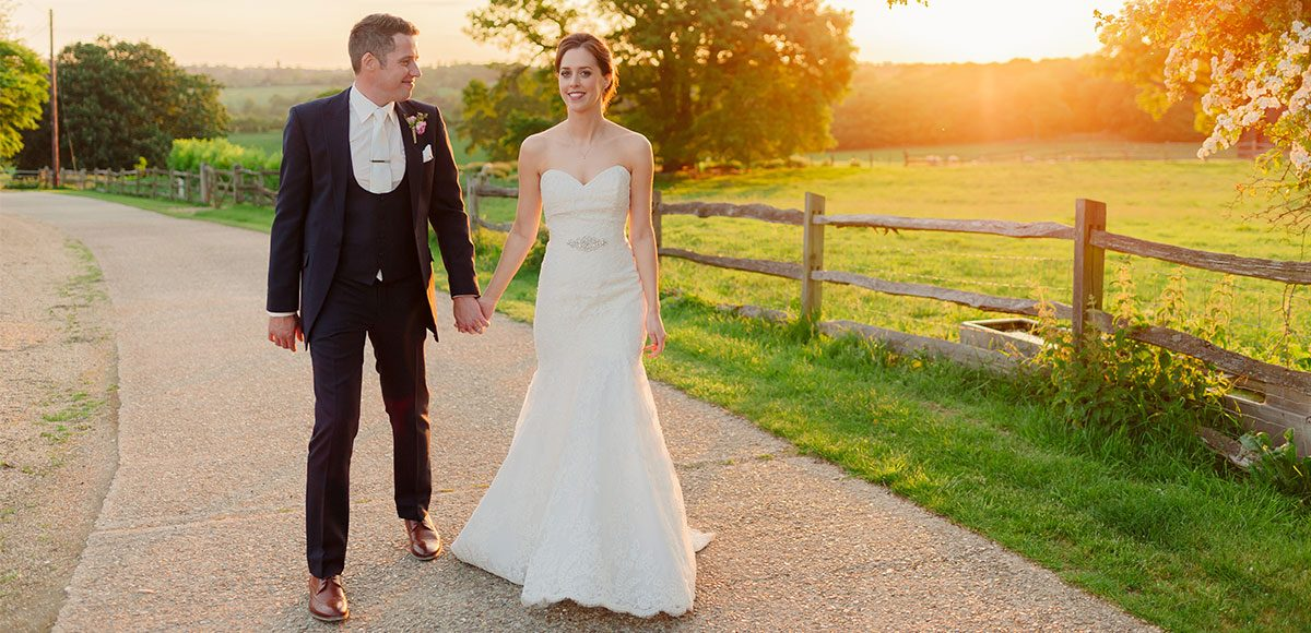 Bride and groom enjoying the sunset over the fields of Gaynes Park