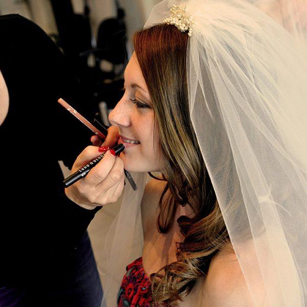 Bride getting her make-up done for a Gaynes Park wedding