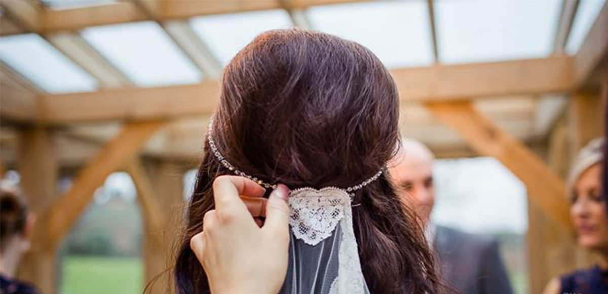 Close up of bride's lace veil during her barn wedding ceremony