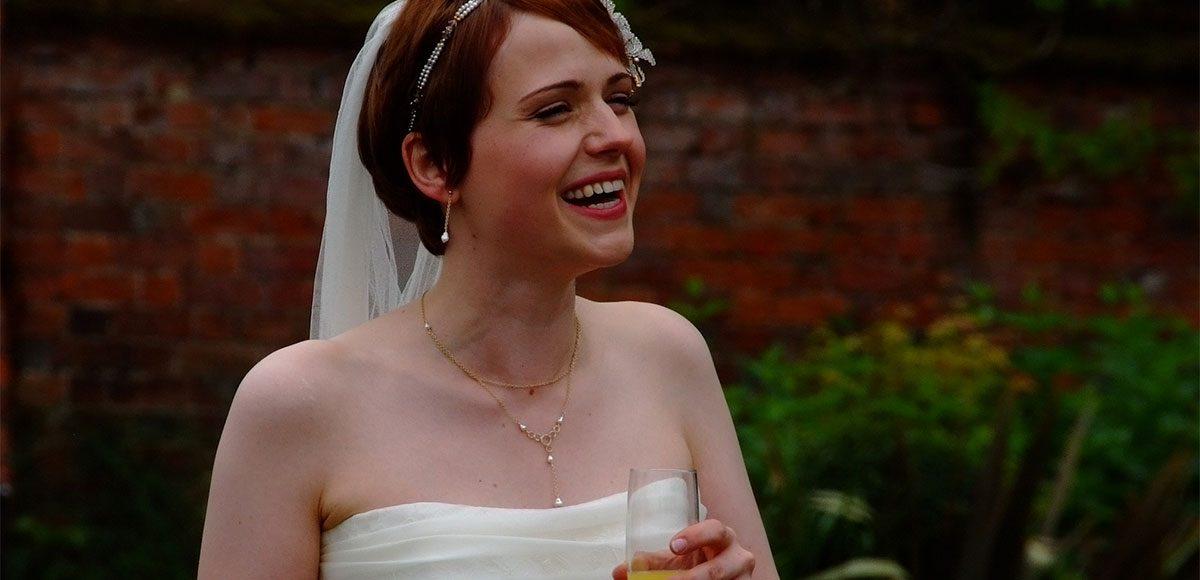 Bride smiling enjoying the wedding reception at Gaynes Park
