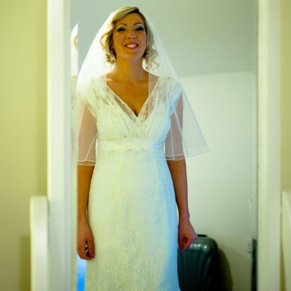 Bride looking at her dress in the mirror just before her wedding ceremony at Gaynes Park