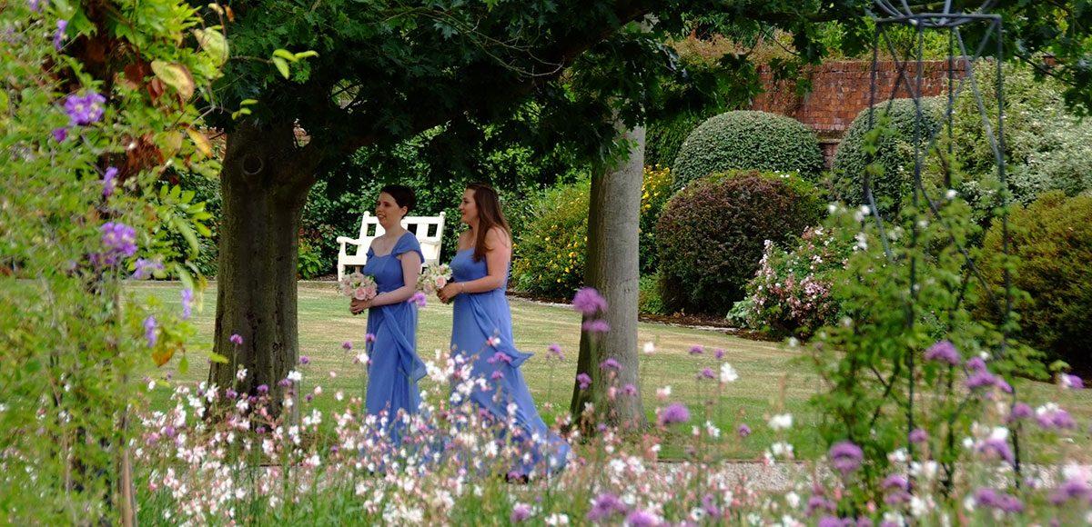 Bridesmaids in blue dresses walking down the Long Walk at Gaynes Park.