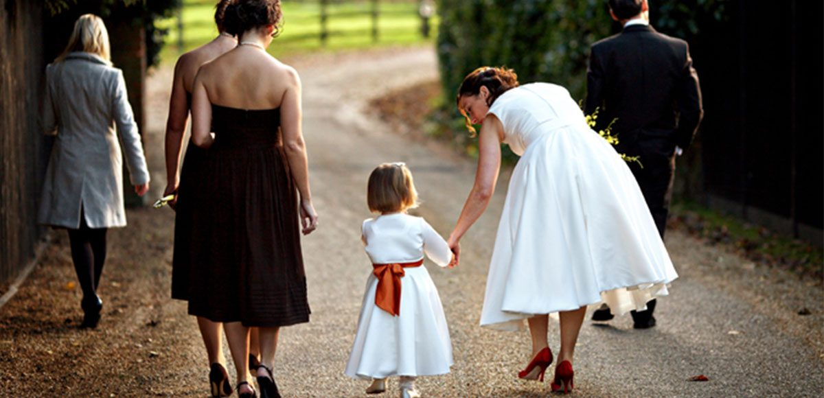 The bride and her bridesmaids make their way to the walled garden to begin the long walk to the civil ceremony