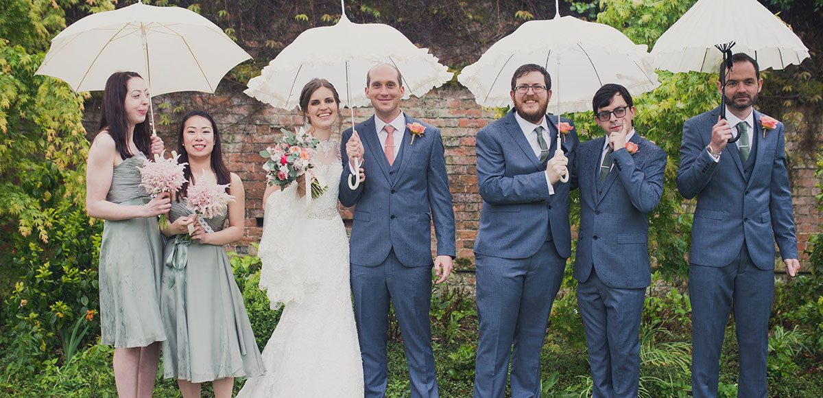 Bridal party posing for photos in the gardens of Gaynes Park wedding venue in Essex
