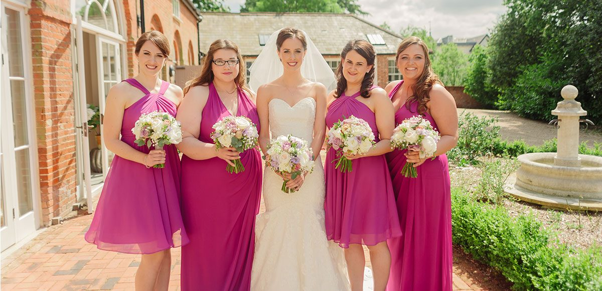 Bride and bridesmaids in bright pink dresses outside the Coach House