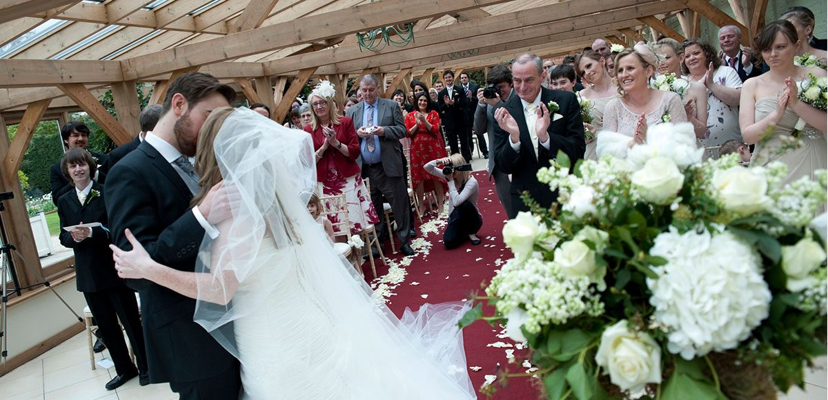 Bride and groom kiss at their Gaynes Park wedding ceremony – wedding packages Essex