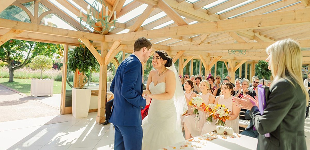 The bride and groom say their vows in the orangery at Gaynes Park