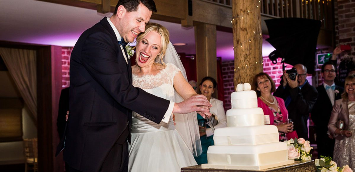 Bride and groom cutting the cake at Gaynes Park – barn wedding venues