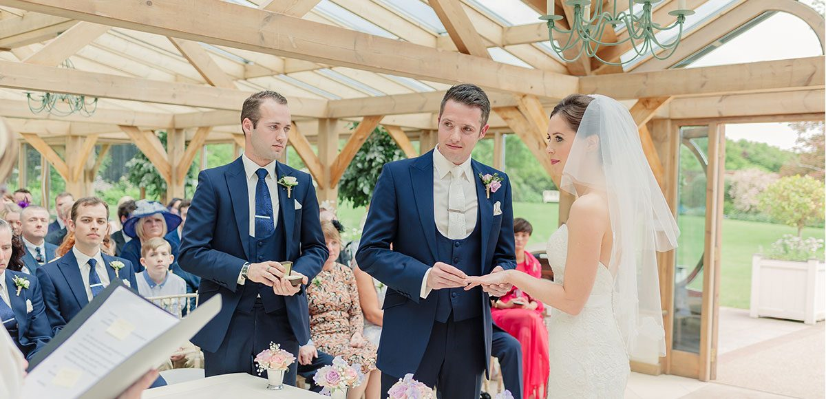 Bride and groom exchanging rings in the Orangery – venues in Essex