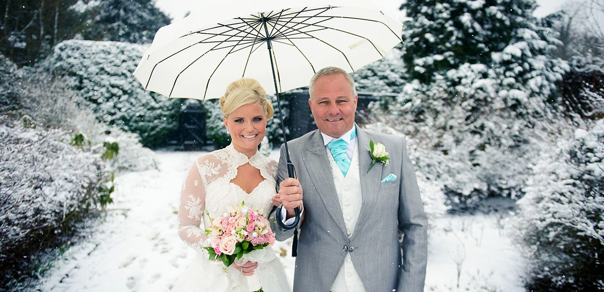 Father of the bride and bride in the snowy garden