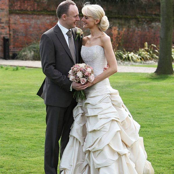 Bride with ruffled wedding dress and groom in gardens of their wedding venue in Essex