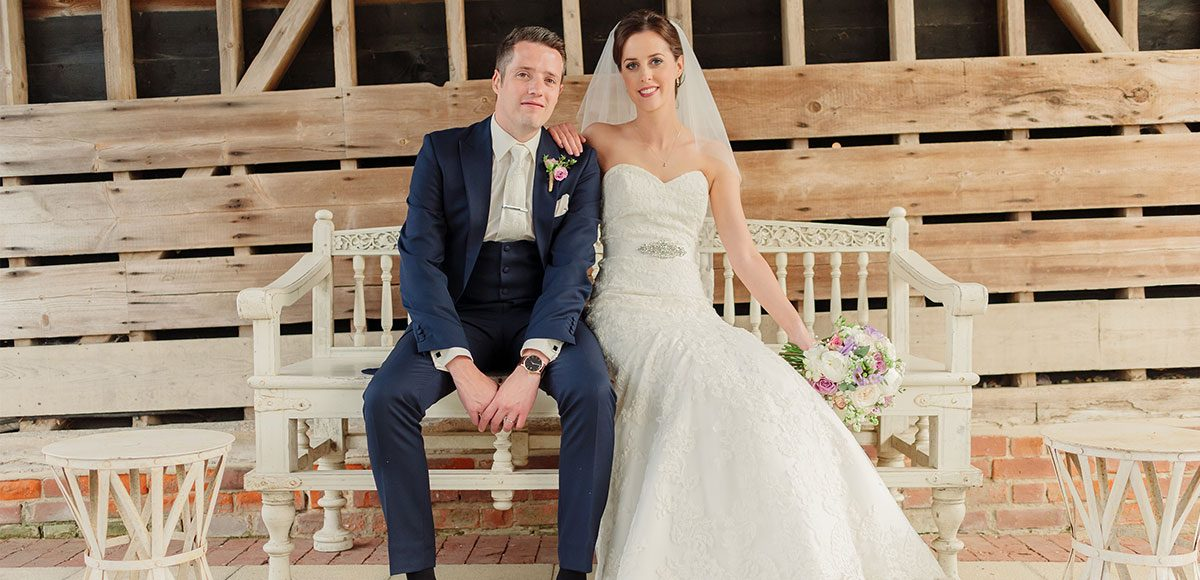 Bride and groom posing in the Gather Barn at Gaynes Park – wedding barns Essex