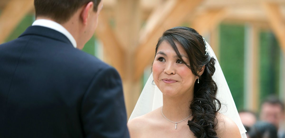 Bride and groom taking their vows in the Orangery at Gaynes Park – Essex wedding