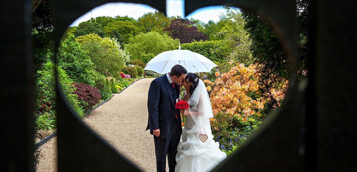 Bride and groom posing in the gardens of Gaynes Park wedding venue in Essex