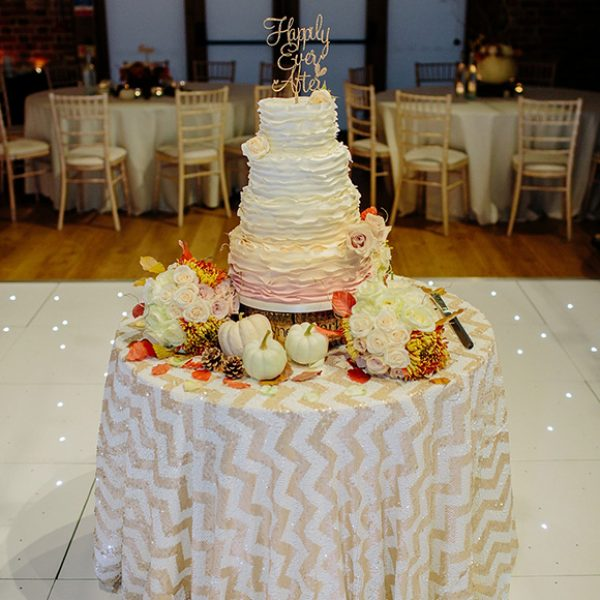A magnificent ombre wedding cake covered in blush and cream iced ruffles with iced rose features
