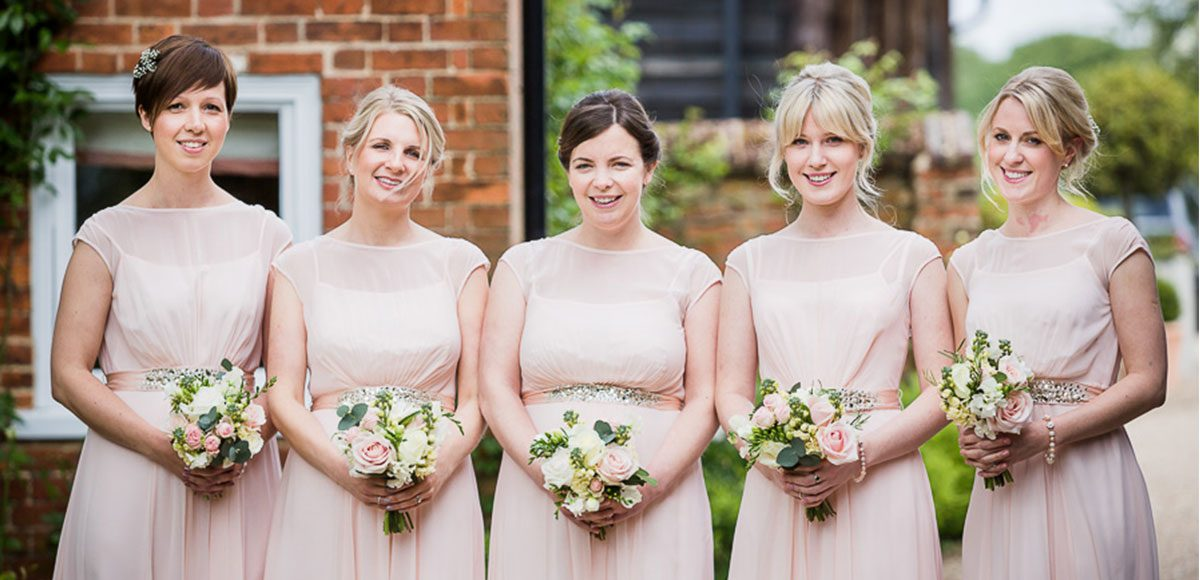 Bridesmaids with peachy pink dresses for a Gaynes Park wedding