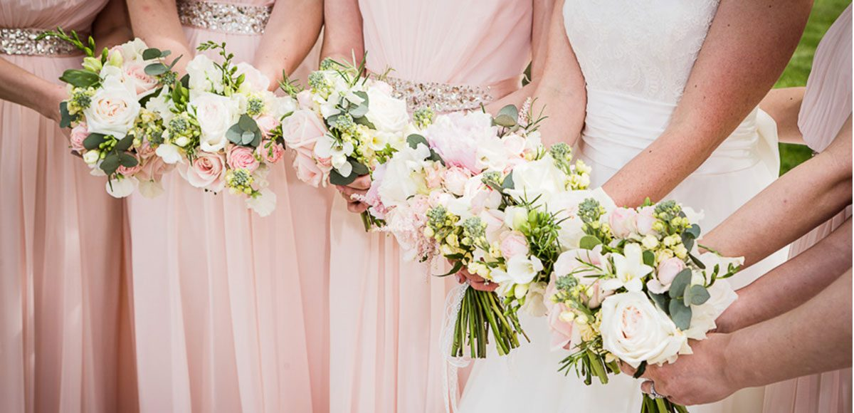 Bridesmaids holding peach and pink wedding bouquets for an Essex wedding