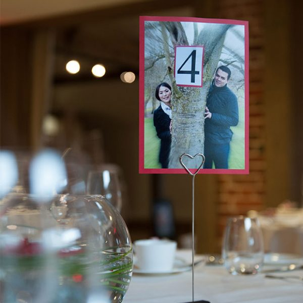 : Photos used to decorate table names for wedding reception – barn hire Essex