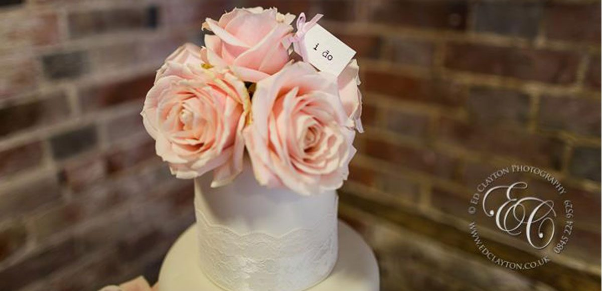 Pretty ivory wedding cake with pink roses at a barn wedding reception in Essex