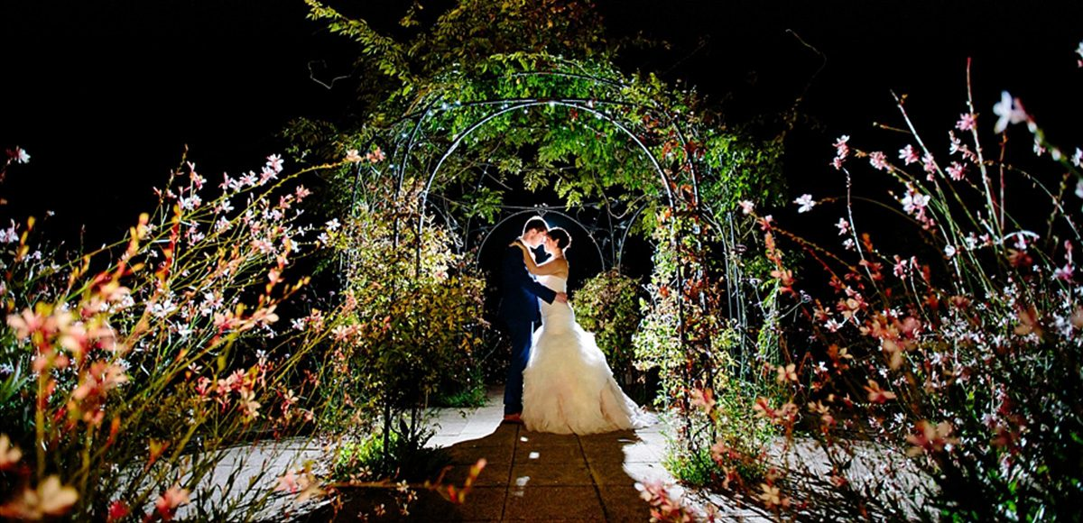 Wedding photograph underneath the pavilion in the walled garden at gaynes park at night
