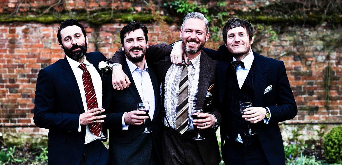 Groomsmen in the gardens of Gaynes Park enjoying the wedding reception
