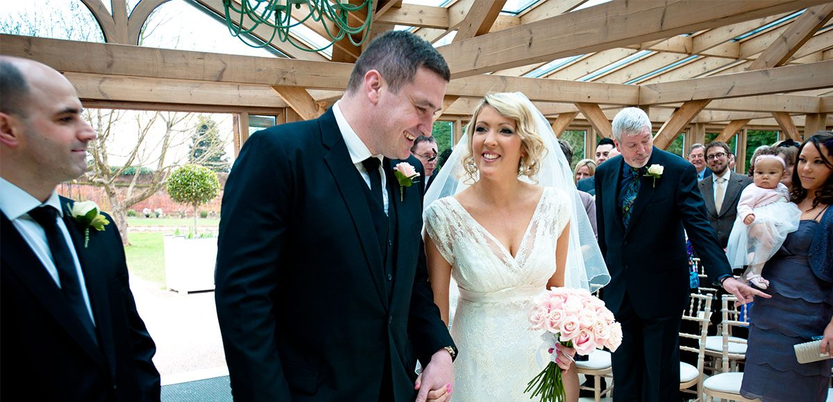 Bride and groom during their wedding ceremony at Gaynes Park in Essex