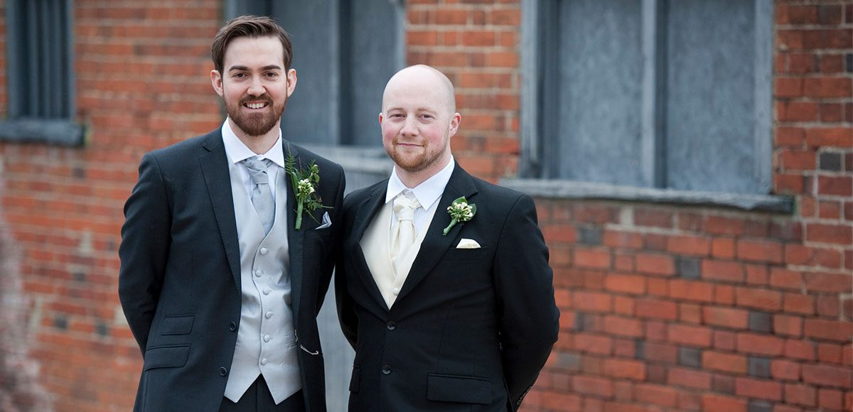 Groom and best man posing for a photo in the grounds of Gaynes Park