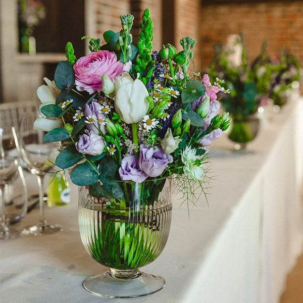 Flowers in a glass urn to decorate tables at Gaynes Park wedding