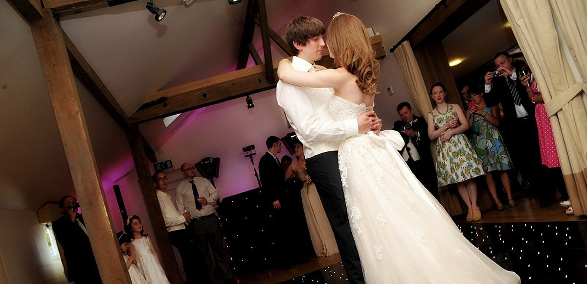 The bride and groom take to the dancefloor for their first dance together in front of their wedding guests