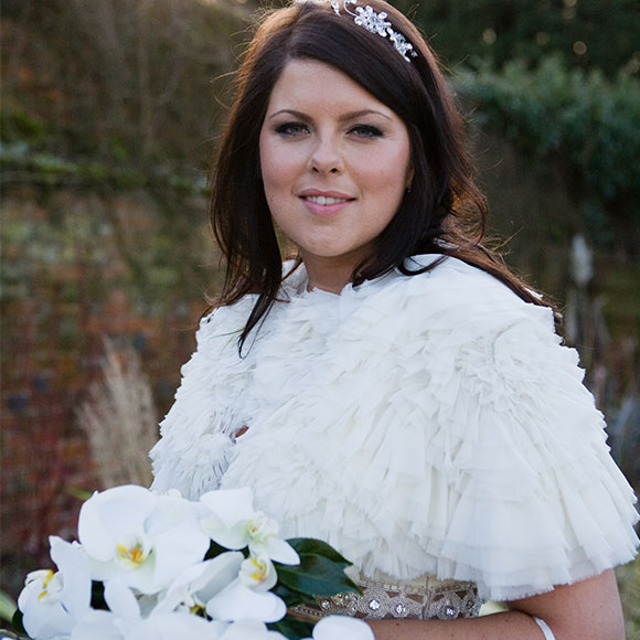 Winter bride with shawl and flowers at her barn wedding reception