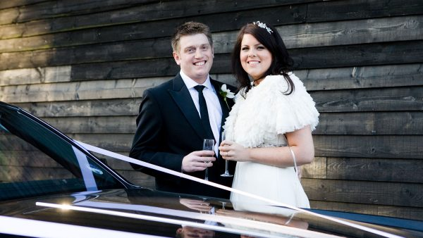 Bride and groom with their vintage wedding transport