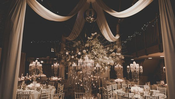 The Mill Barn is decorated with white drapes and candelabras for a beautiful winter wedding